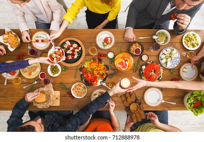 Friends dinner table top view. People eat healthy food together, home party