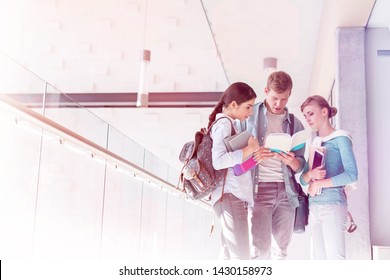Friends discussing over book while standing in corridor at university