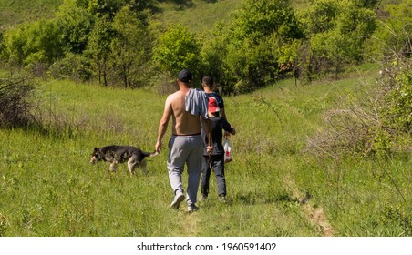 Friends with dog walking on the green hill on a sunny spring day. Country road landscape with people in walk. Rear view. Vatra Dornei, Maramures, Romania, May 29, 2020
