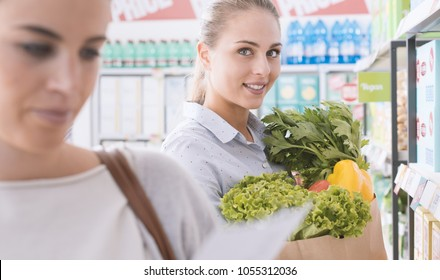 Friends doing grocery shopping together at the supermarket, one is holding a bag with fresh vegetables and smiling