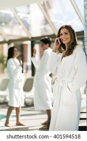 Friends dressed in bathrobes relaxing in a spa next to a swimming pool