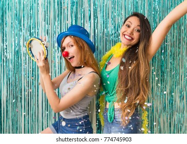 The friends are dressed for Carnaval. Blue background. Women dance samba and play tambourine.