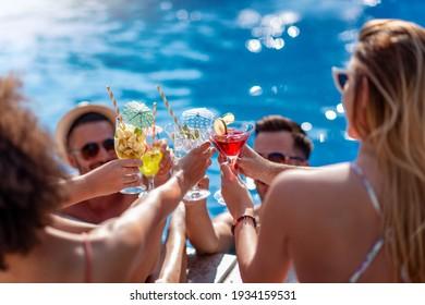Freunde trinken im Sommerurlaub Cocktails am Pool und vergnügen sich miteinander. Menschen, Liebe, Sommer, Urlaub und Lifestyle Konzept.