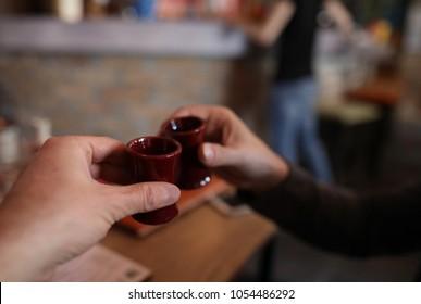 Friends drink sake in a Japanese restaurant.