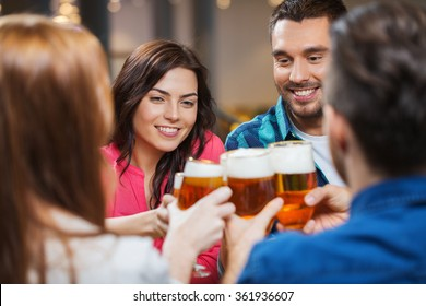 friends drinking beer and clinking glasses at pub