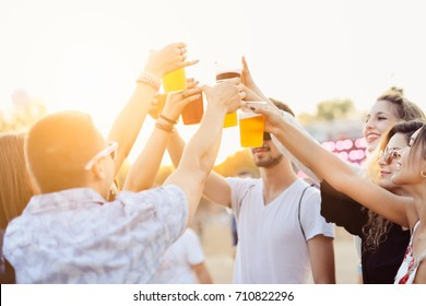 Friends drinking beer and having fun at music festival. Cheers