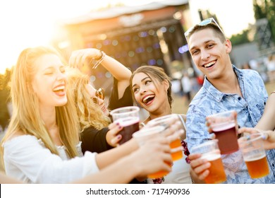 Friends drinking beer and having fun at music festival