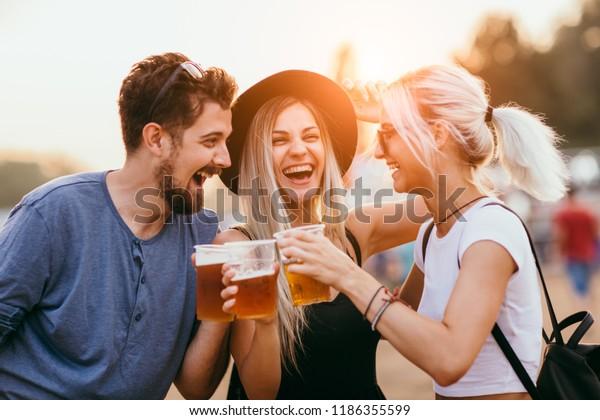 Amigos tomando cerveza y divirtiéndose en el festival de música