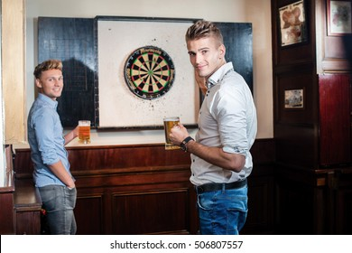 Friends drinking beer in the pub and playing darts