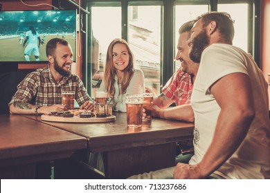 Friends drinking beer and watching soccer in a pub