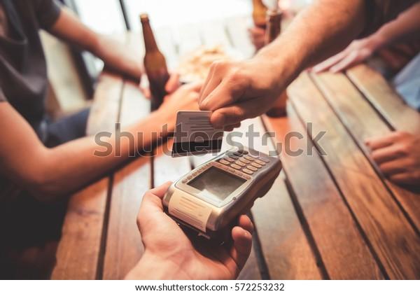 Freunde trinken Bier, während sie in der Kneipe ruhen. Bild von einem Typ, der mit Kreditkarte bezahlt