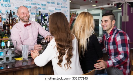 Friends drinking and chatting with happy adult barman at bar counter