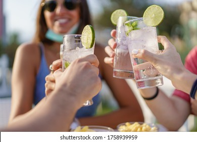 Friends drinking cocktails in an outdoors snack bar restaurant in the summer wearing face mask on to be protected from coronavirus - Happy people cheering with mojito and having fun - Shutterstock ID 1758939959