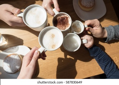 Friends drinking coffee in cafe. Family get rest together with a cup of coffee. Happy family sunny day in cafe.