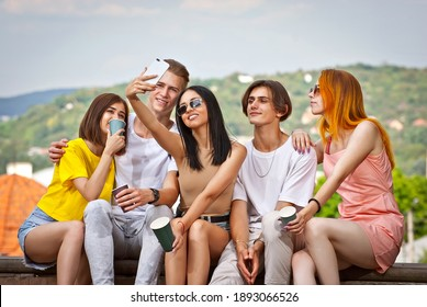Friends drinking coffee on the background of the city. Boys and girls are smiling. Teenagers sitting on the curb on a sunny day in the square. Young people taking selfies.