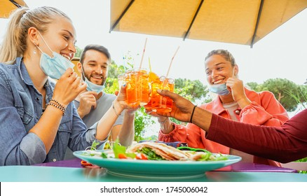 Friends drinking coktail and eating snack tapas in a restaurant bar outside in summer days with face mask on to be protected from coronavirus - Happy people cheering with spritz and having fun