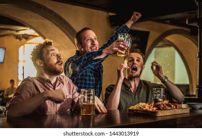 Friends drinking draft beer and watching tv in a pub
