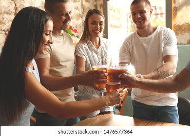 Friends drinking fresh beer in pub