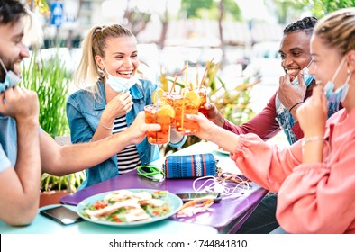 Friends drinking spritz at cocktail bar with face masks - New normal friendship concept with happy people having fun together toasting drinks at restaurant - Bright end filter with focus on left woman
