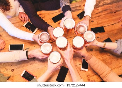 Friends drinking and toasting beer at pub brewery - Group of people cheering with pint of beer over wooden table with smartphones, top view, close up on hands - Friendship and lifestyle in London