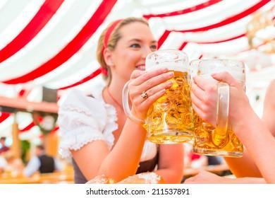 Friends drinking together Bavarian beer in national costume or Dirndl on Oktoberfest