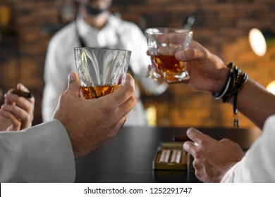 Friends drinking whiskey together in bar, closeup