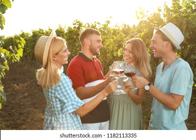 Friends drinking wine and having fun at vineyard