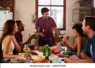 Friends with drinks at the table during a dinner party