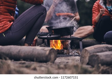 Friends eat from a traditional cast iron pot around a campfire