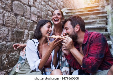 Friends eating delicious pizza at street