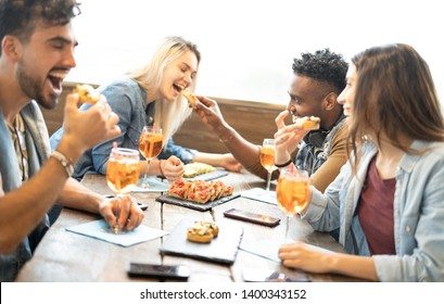 Friends eating and drinking spritz at fashion cocktail bar restaurant - Friendship concept with young people having fun together with drinks and food on happy hour at pub - Focus on pizza slices