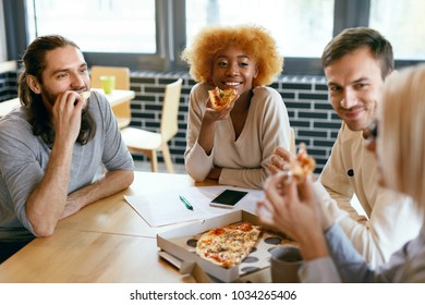 Friends Eating Food In Cafe. People Eating Pizza At Lunch Break. Beautiful Young Men And Women Sitting At Table, Talking And Sharing Pizza Together. Nutrition. High Quality Image