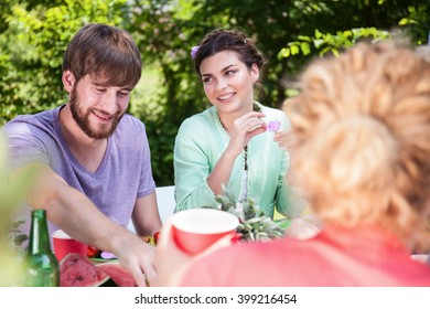 Friends eating outdoor at summer garden barbecue party