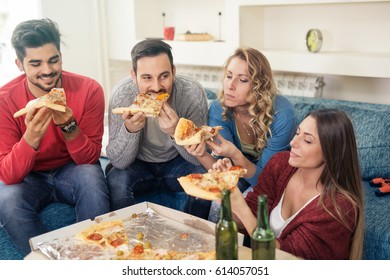 Friends eating pizza at home party,having fun together.