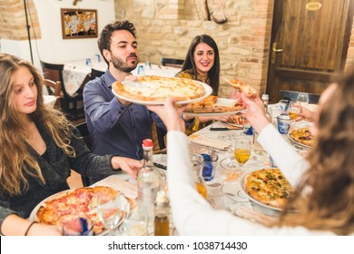 Friends eating pizza together and sharing platters. Group of friends together at restaurant enjoying proper Italian pizzas. Friendship and Italian food concepts.