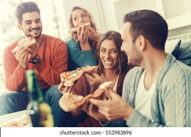 Friends eating pizza.They are having party at home, eating pizza and having fun.