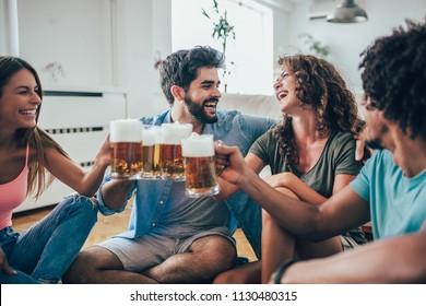 Friends eating popcorn and drinking beer mug at home, having fun.