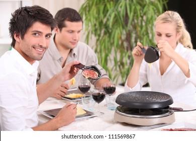 Friends eating raclette
