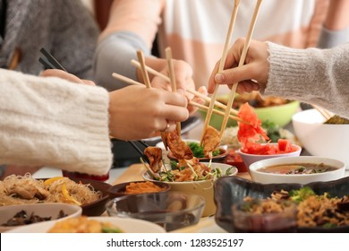 Friends eating tasty Chinese food at table