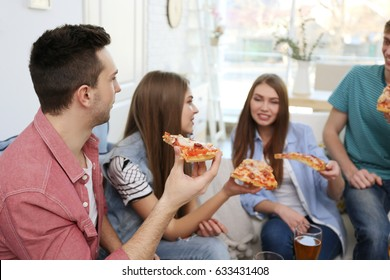 Friends eating tasty pizza at home party