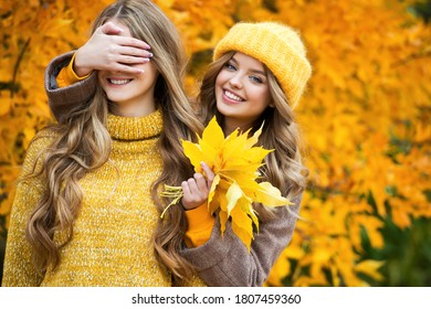 Friends enjoy an autumn day in the Park. Young happy women with yellow autumn leaves