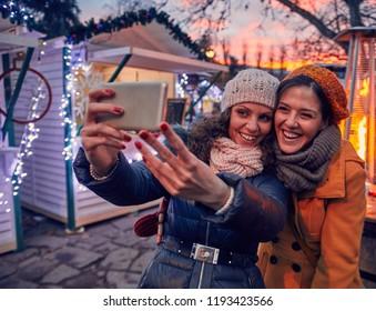 Friends Enjoying Christmas Market And Making Selfie