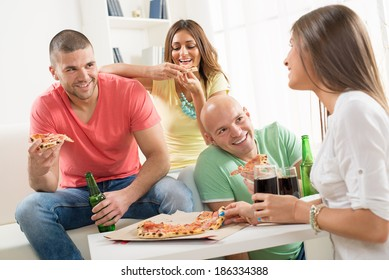 Friends enjoying eating pizza and drink a beer together at home party.