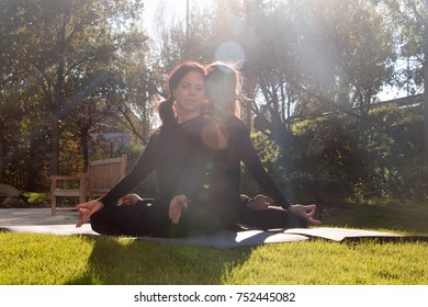 Friends enjoying relaxing yoga outdoors in the park.
