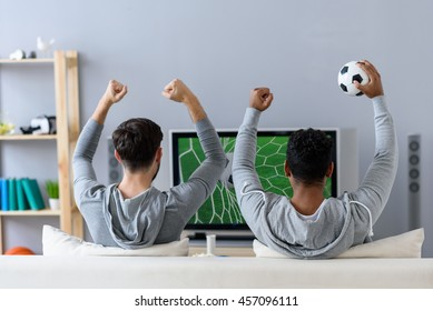 Friends enjoying soccer in TV
