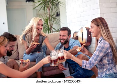 Friends enjoying together at home,eat pizza and drink beers.