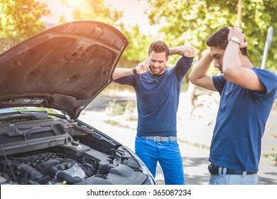 Friends examining broken down car on sunny day