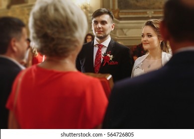 Friends and family congratulate newlywed couple in church, emotional bride and groom tearing up while receiving  wedding presents after ceremony