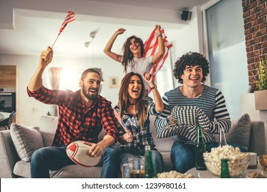 Friends are fans of sports games as American football love spending their free time at home together. They are screaming and gesturing for a victory.