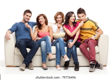 friends feeding popcorn to each other while sitting couch